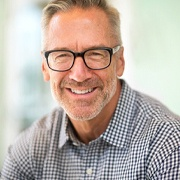 Smiling senior man with glasses and All-on-4 dentures