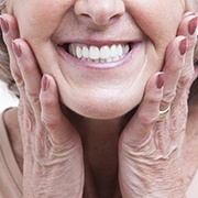 older woman holding face with dentures in Pepper Pike