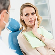 Woman with toothache asking questions about emergency dentistry