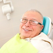An older man smiling while in the dentist's chair
