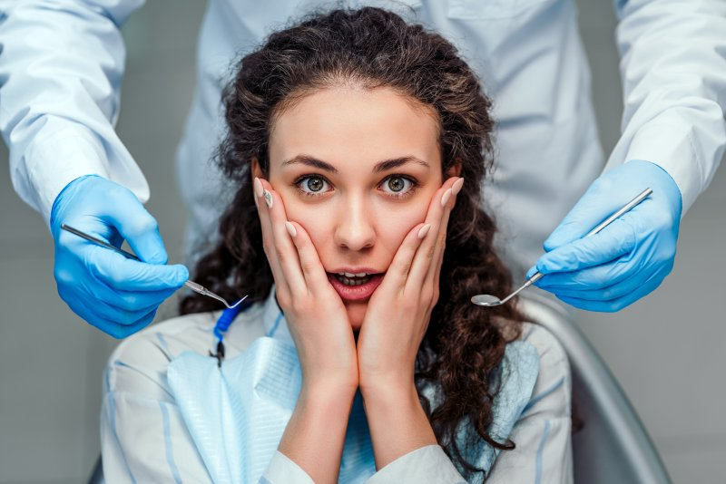 a young woman holds her face between her hands and looks anxious while a dentist stands behind her with dental instruments in their hands