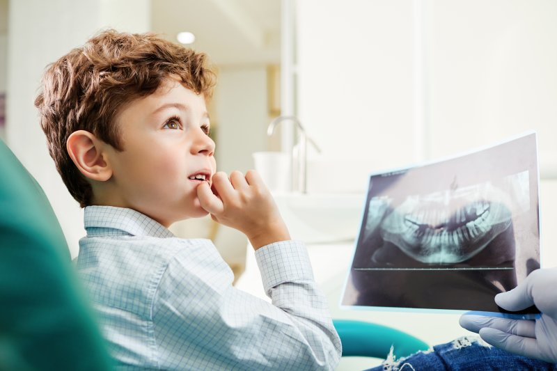 Child looking at dentist and dental X-ray