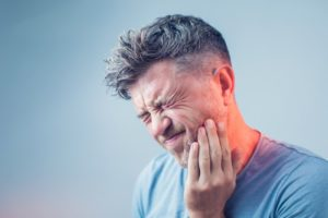man with a toothache holding his cheek in pain